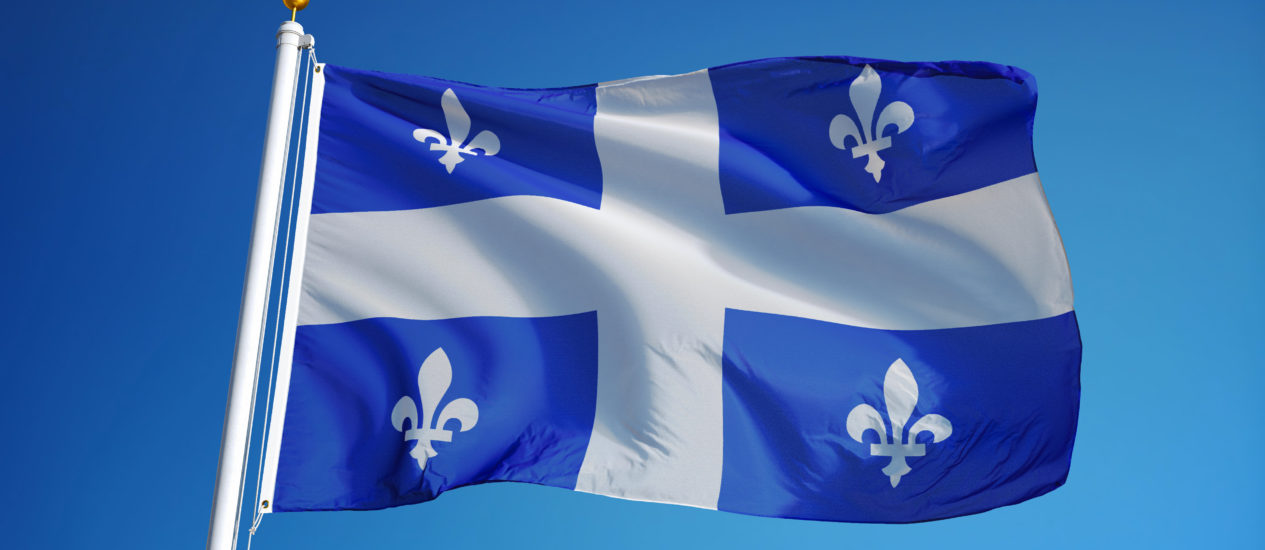 Quebec flag waving against clean blue sky, close up, isolated with clipping path mask alpha channel transparency